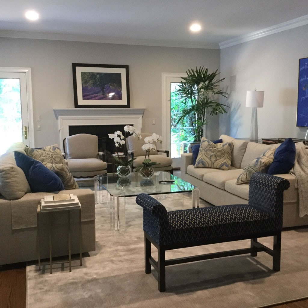 Living room with sofa, love seat, two chairs and bench in shades of taupe and navy.