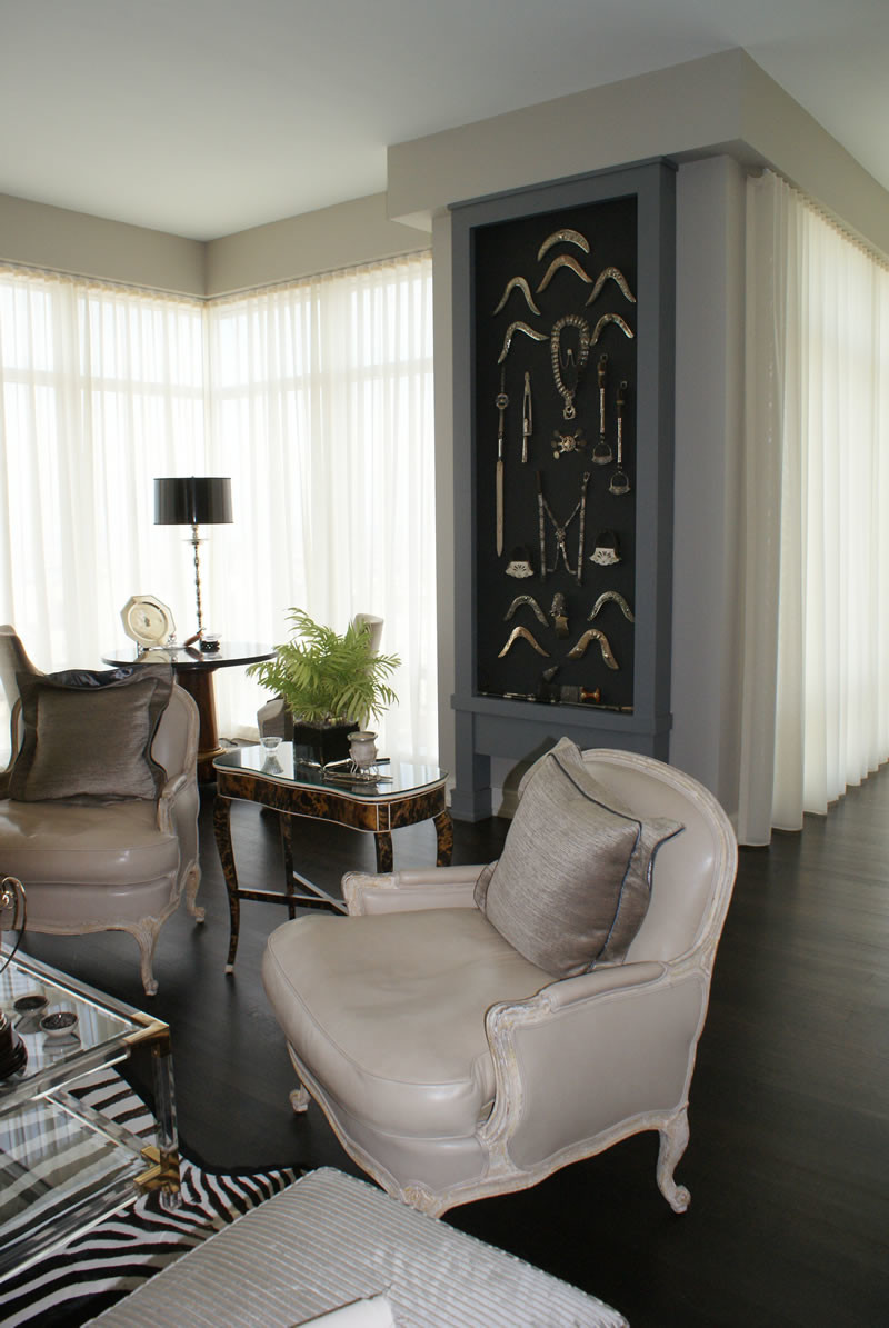Pair of soft taupe leather covered antique chairs on dark wood floors showcasing floor-to-ceiling sheer sheathed windows.