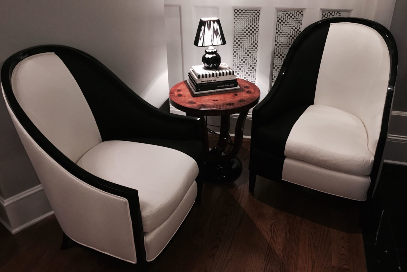 Two black and white modern upholstered chairs for Hillary Clinton with small round wood end table topped with lamp perched on black and white covered books.