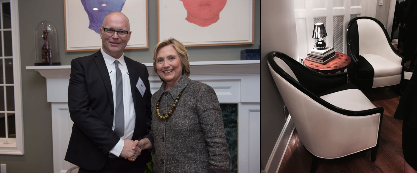 Man shaking hands with gray suit wearing Hillary Clinton in front of white fire place and Additional angle of black and white modern upholstered chairs for Hillary Clinton with small round wood end table topped with lamp perched on black and white covered books.