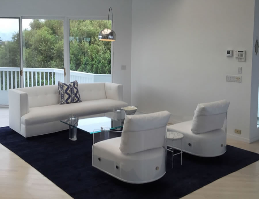 White sofa and two white chairs with acrylic arm-rests divided by clear acrylic coffee table sitting on blue area rug in all white walled room facing glass doors that open to white patio.