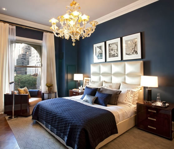 Bedroom with white satin upholstered headboard, two end tables, reading chair next to sheer paneled window overlooking New York City.
