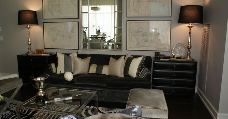 Livingroom featuring soft gray covered sofa, zebra rug, acrylic table, and mirror reflected view of home.